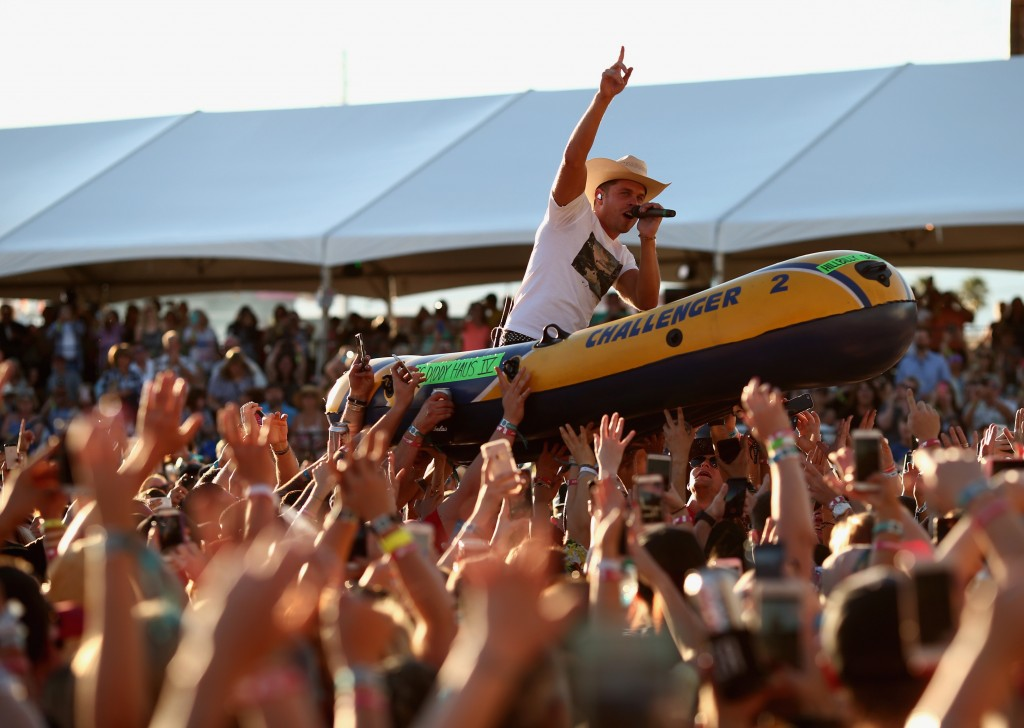 Dustin Lynch rides a raft over the crowd while performing at the 4th ACM Party for a Cause Festival at the Las Vegas Festival Grounds on April 2, 2016 in Las Vegas, Nevada. (Photo by Christopher Polk/Getty Images for ACM)